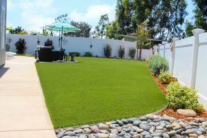 Artificial turf in backyard with patio furniture near walkway