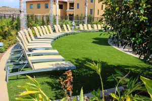 artificial turf lawn with luxury recliners near pool