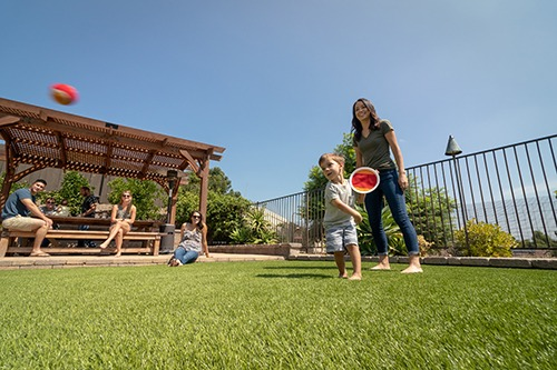 girl overlooks small child playing on artificial turf lawn