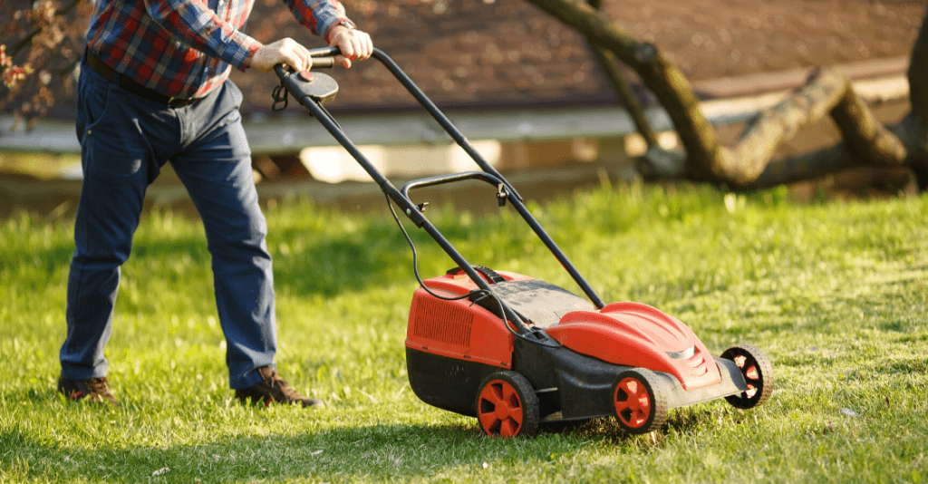 worker mowing the lawn